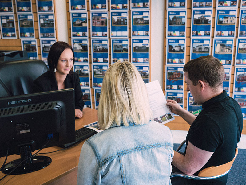 Daniel Henry Staff Member Disussing Mortgage Options With A Young Couple